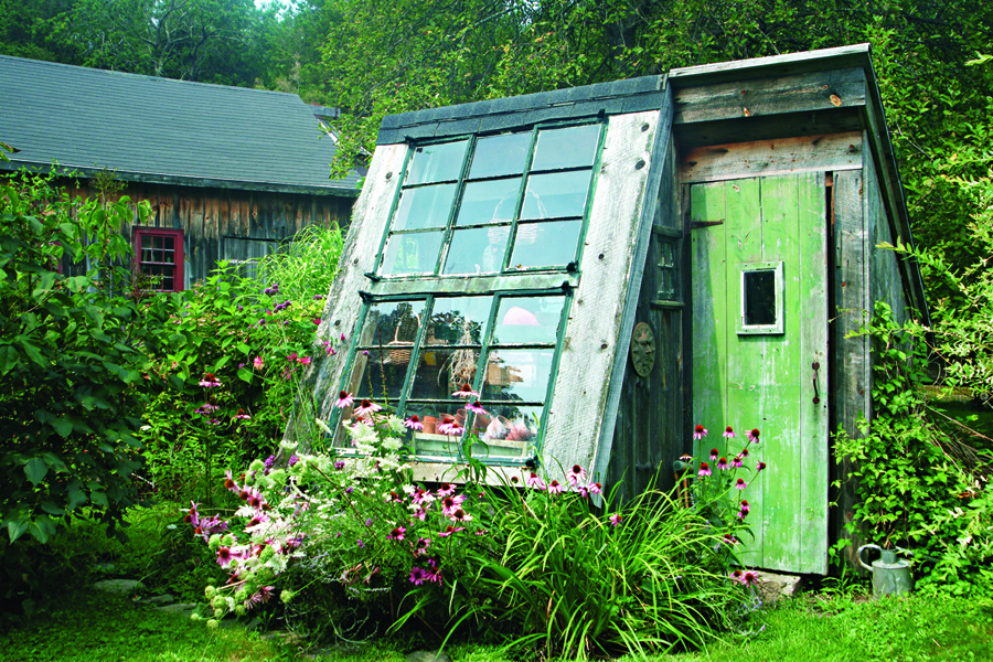 This repurposed cottage with its south-facing window serves as a rustic greenhouse